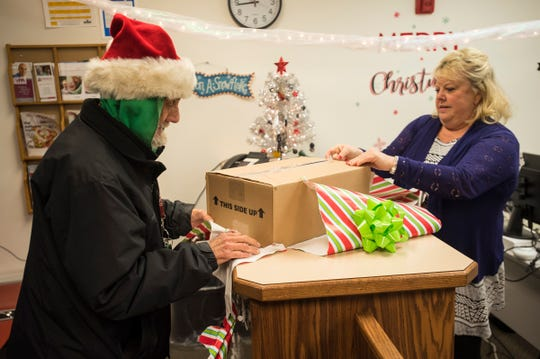 "Pam McDougal, right, helps Tommy ""Spoonman"" Woodard unwrap a box full of festive hats Tuesday, Dec. 18, 2018 in the Public Guardian Office in the St. Clair County Courthouse. McDougal collected the novelty hats to give to Woodard."