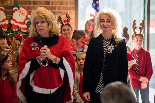 Gardens Elementary fifth grade teachers Denise Gallemore, left, and Tracy Carleton speak at the start of the school's annual Christmas program Tuesday, Dec. 18, 2018 at Vicksburg Hall in Marysville.