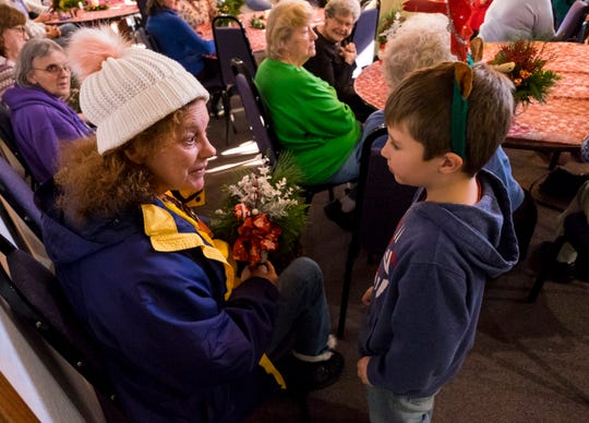 Gardens Elementary first-grader Ozzy Baldock, right, presents a gift to Vickie Nutter as part of the school's annual Christmas program Tuesday, Dec. 18, 2018 at Vicksburg Hall in Marysville.