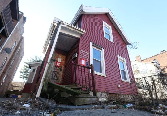 Litter strewn across the front yard and broken porch of the boarded up 556 Main Street in the City of Poughkeepsie on December 18, 2018. The red structure is slated for demolition by the city.