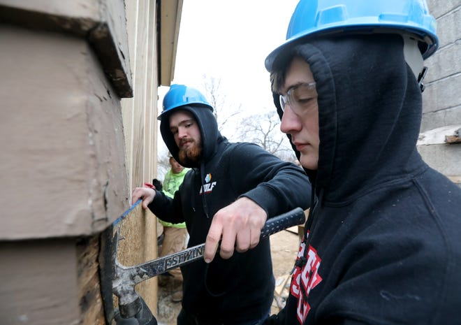 BOCES students Alex Henion and Dillon Callaghan adjust a plywood board while working on a former zombie home on Mt. Read boulevard.