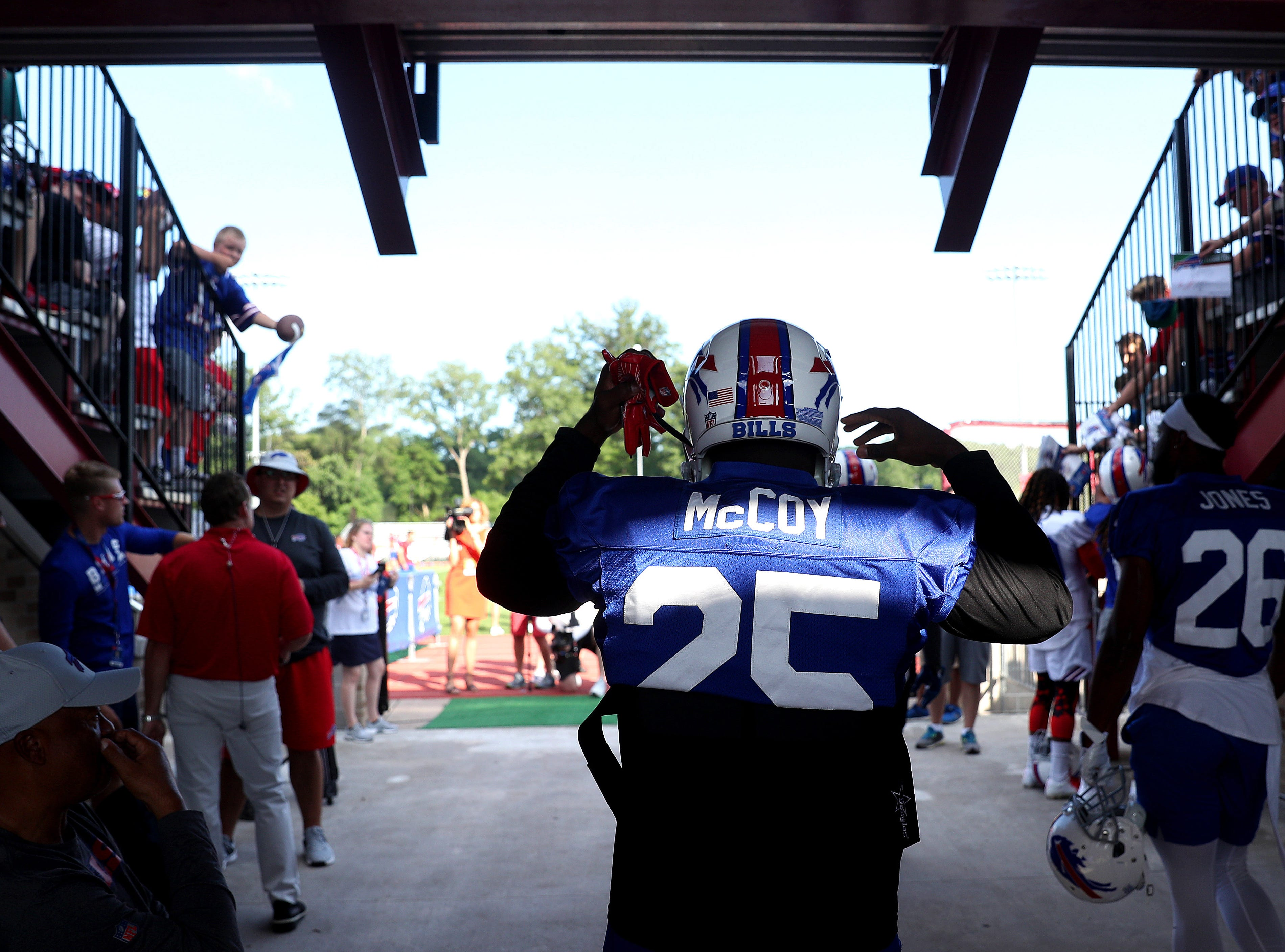 Bills running back LeSean McCoy heads out onto the practice field to cheers from fans on the opening night of training camp at St. John Fisher College.  The star running back is coming in with some off-the-field baggage about a break-in and assault at one of his homes.  I knew he would be the story and I really wanted to make a poignant  photo of him.  When I saw the sliver of light shining through the bleachers as he entered the stadium, I waited until it illuminated his name and fired.