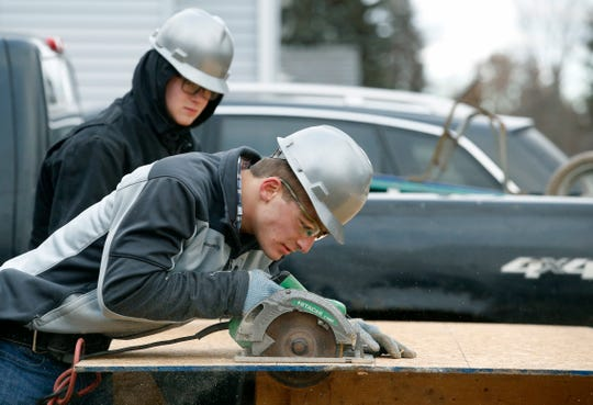 BOCES students Michael Vinci and Shane Graham cut plywood boards while working on a former zombie home on Mt. Read boulevard.