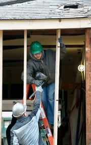 BOCES student Adam Versteeg takes a nail gun to work on a wall at a former zombie home on Mt. Read boulevard.