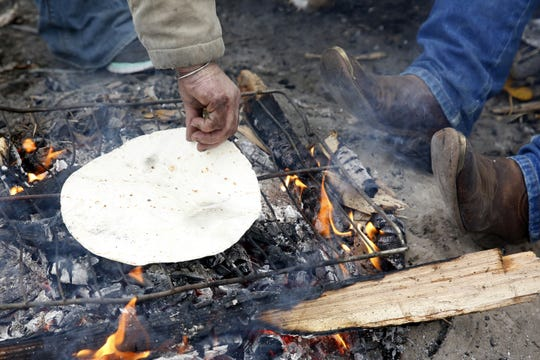 Toni warms a tortilla over the fire for breakfast as Art Scaglione warms his boots at Toni's camp in Wallace Marine Park in Salem, Oregon, on Friday, Dec. 7, 2018.