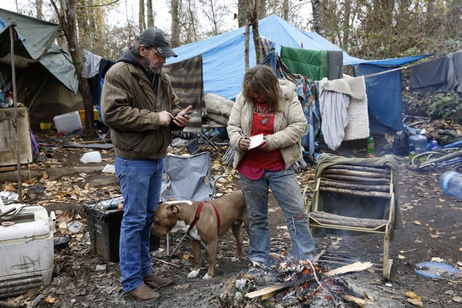Art Scaglione (left) reads a phone number for Toni to copy down while standing in her camp in Wallace Marine Park in Salem, Oregon, on Friday, Dec. 7, 2018.