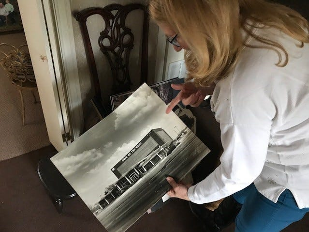 Laura Gillis, co-owner and photographer for Barney's Studio, 3111 W Beauregard Ave., showing a picture of the old Bank of the West Dec. 18, 2018.