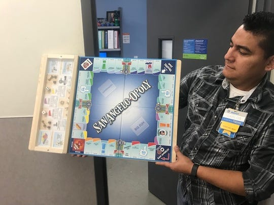 Walmart assistant manager Carlos Quiroga holds up a San Angelo-Opoly game at the 3440 S. Bryant Blvd location.