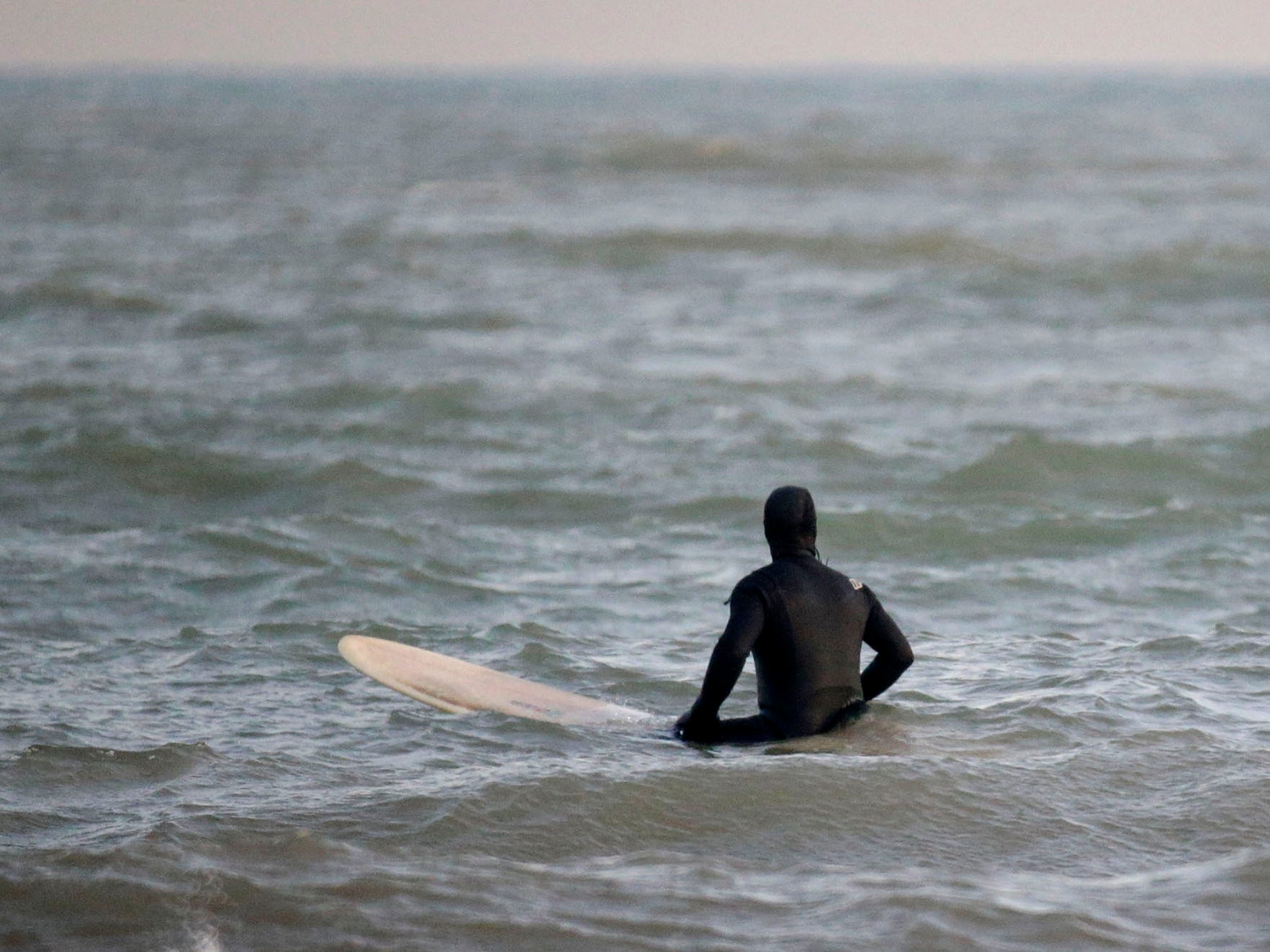 Brian David watches for a wave at the lakefront, Tuesday, December 18, 2108, in Sheboygan, Wis.