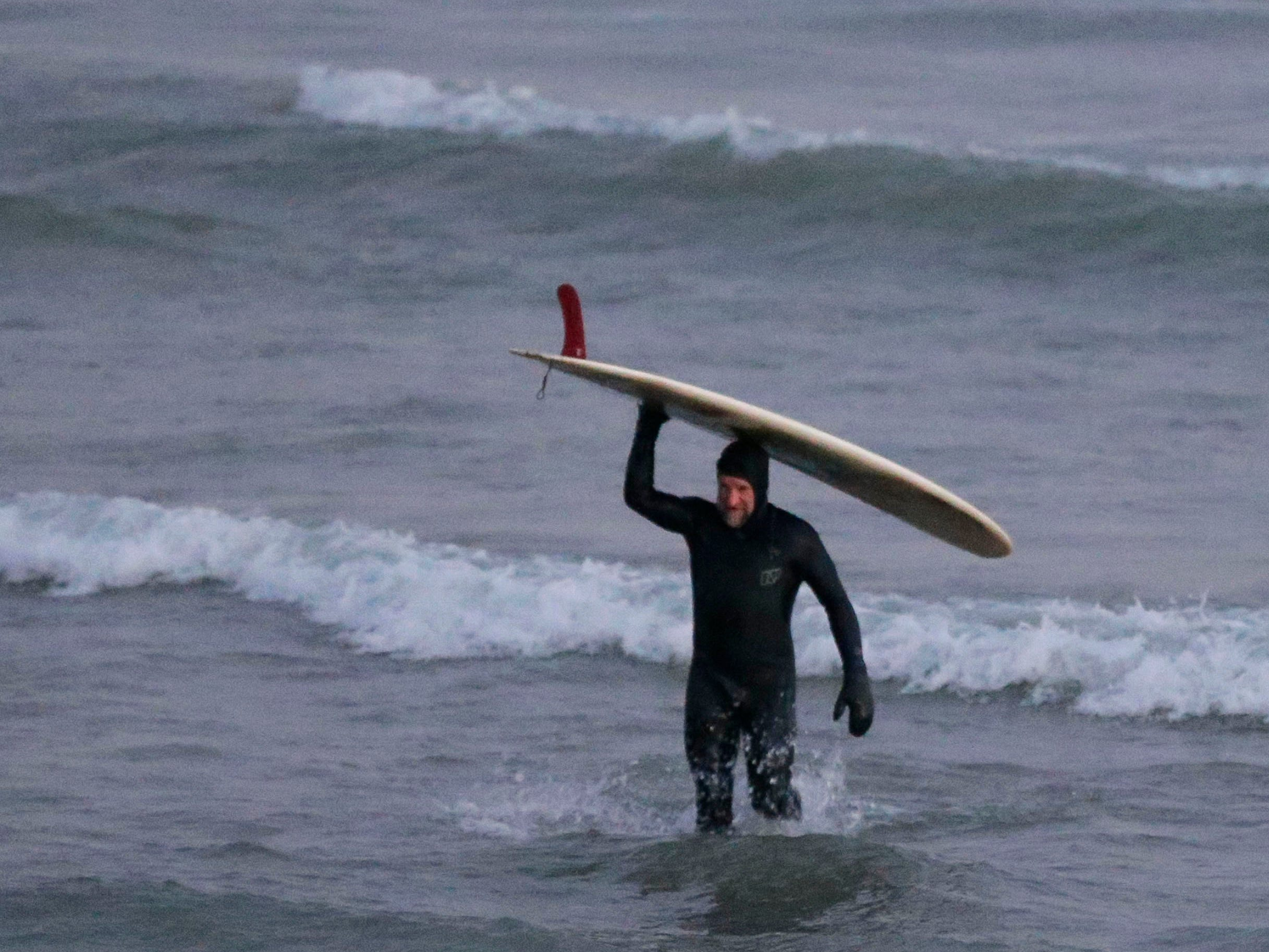 Brian David walks up to land after surfing at the lakefront, Tuesday, December 18, 2108, in Sheboygan, Wis.