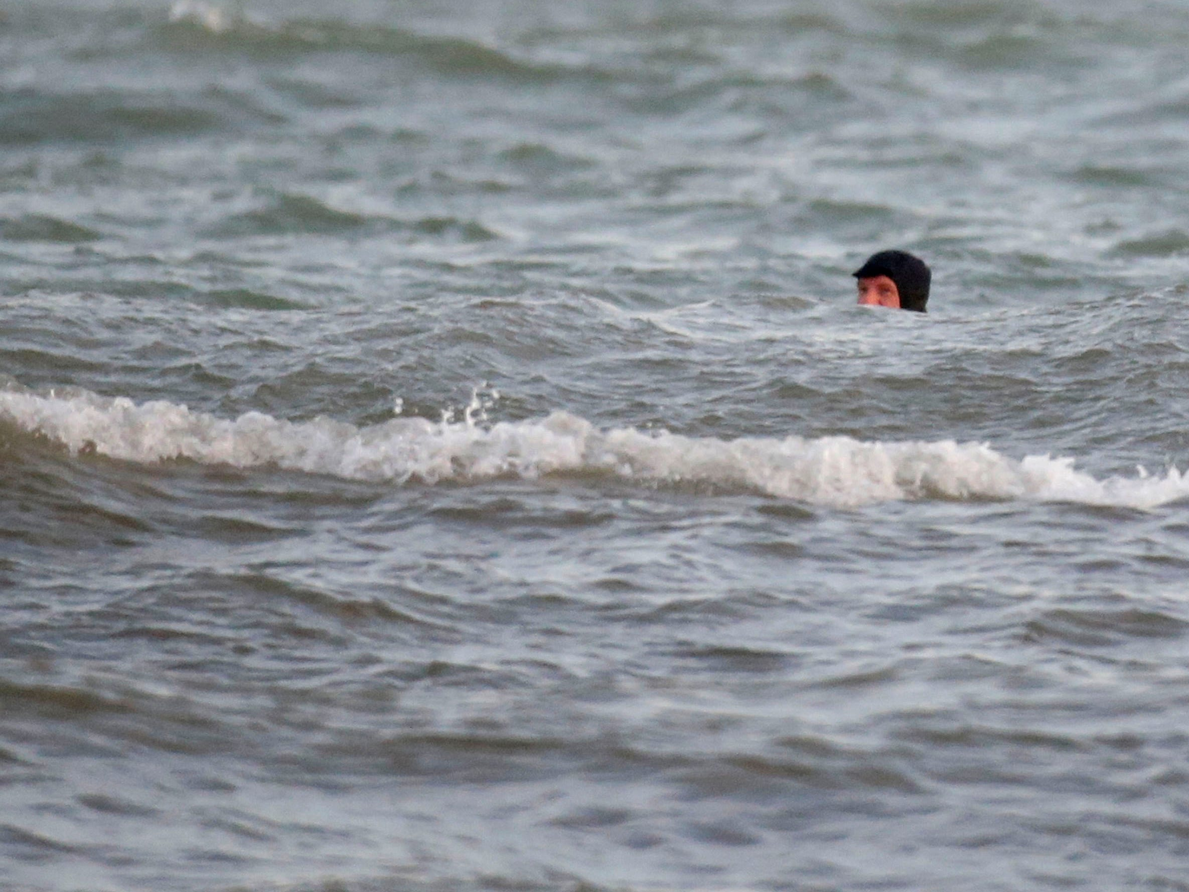 Brian David peers over the water while waiting for the right wave at the lakefront, Tuesday, December 18, 2108, in Sheboygan, Wis.