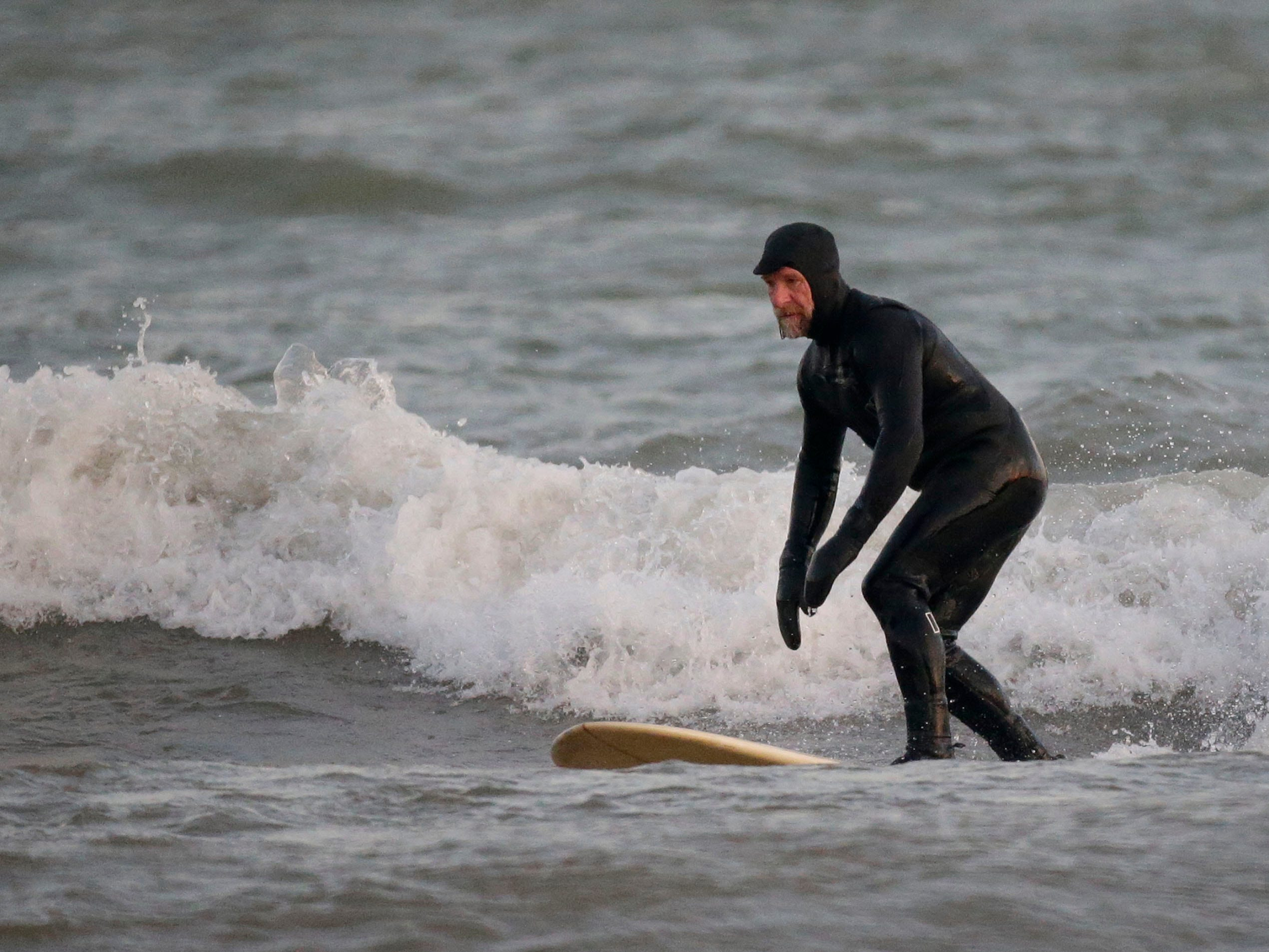 Brian David surfs at the lakefront, Tuesday, December 18, 2108, in Sheboygan, Wis.