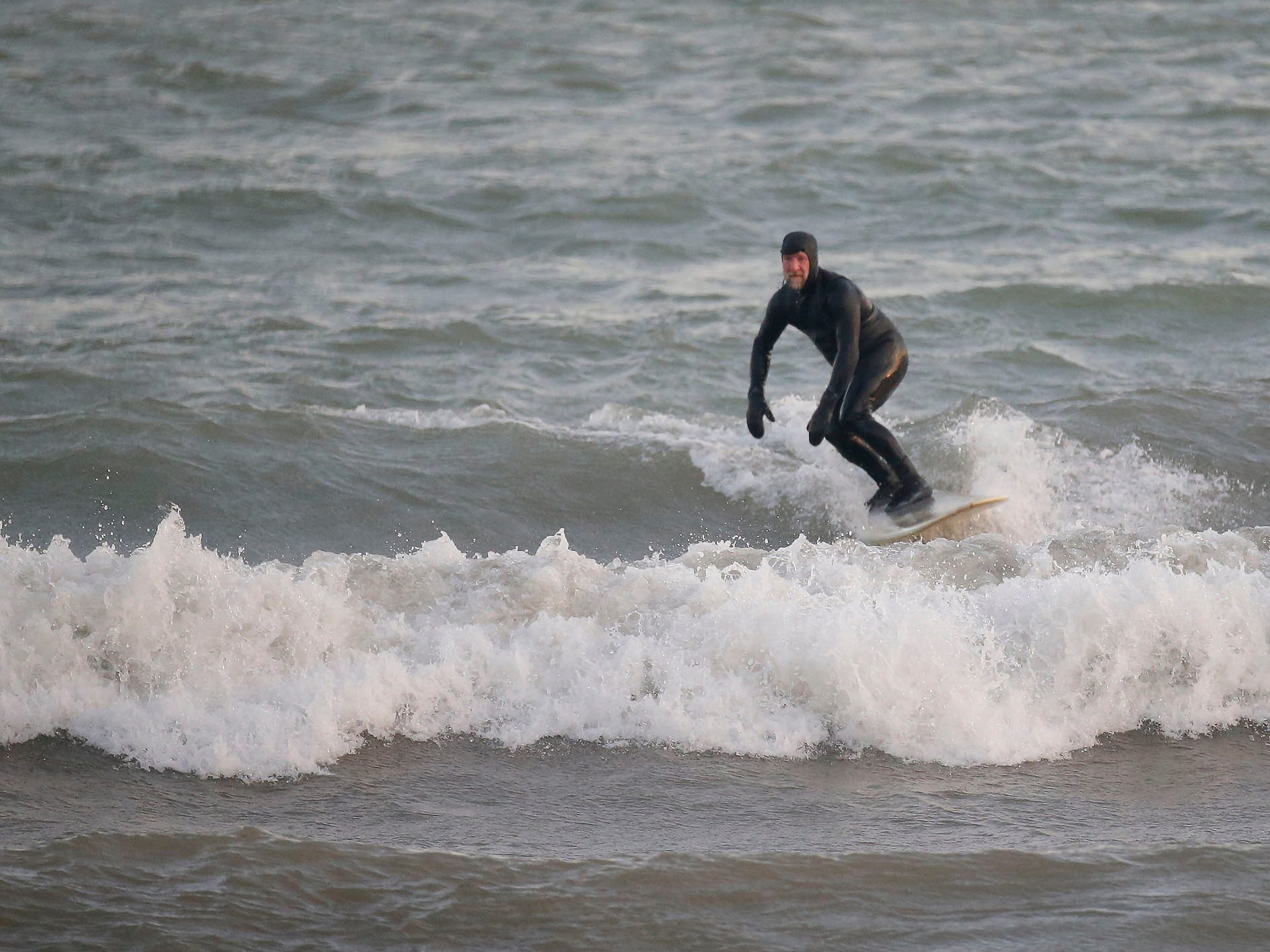 Brian David cuts into a wave at the lakefront, Tuesday, December 18, 2108, in Sheboygan, Wis.