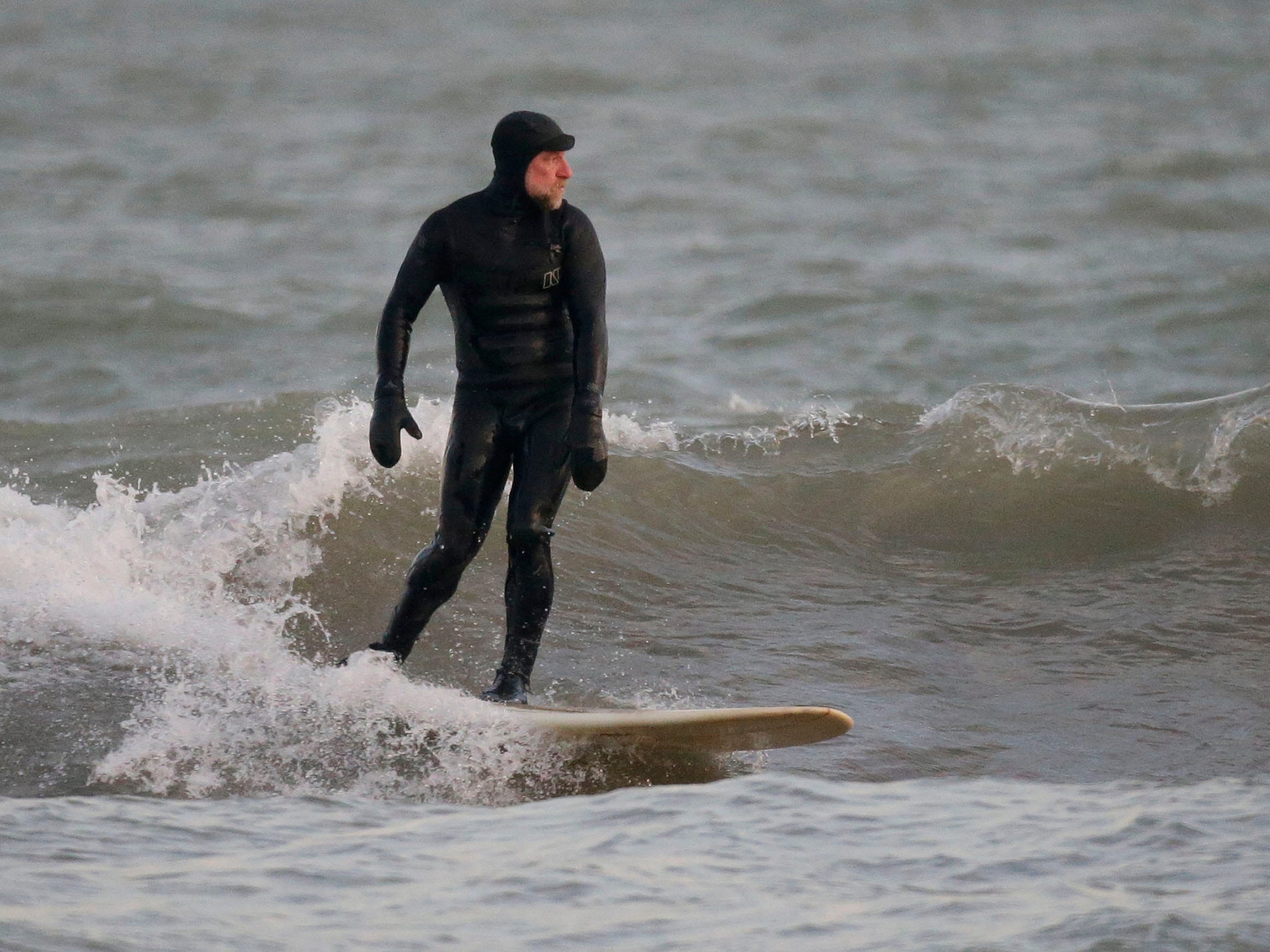 Brian David glides on a wave, Tuesday, December 18, 2108, in Sheboygan, Wis.