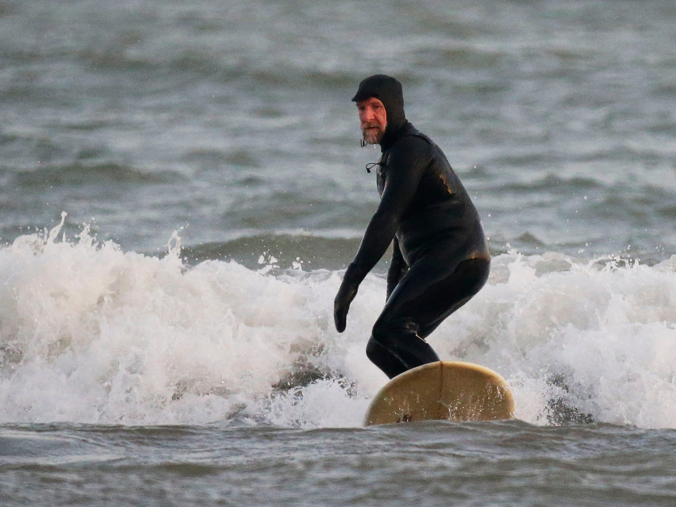 Brian David of Milwaukee takes on the waves at the lakefront, Tuesday, December 18, 2108, in Sheboygan, Wis.