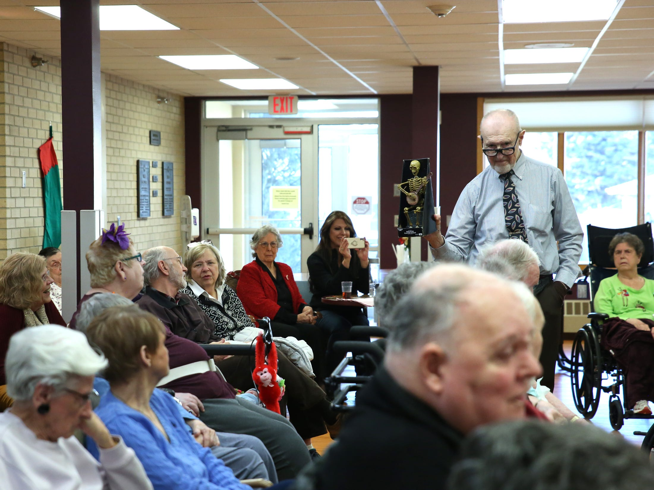 Frank Petereit entertains audience members with a banjo-playing skeleton he bought at Wal-Mart between Dancing Divas performances at Good Samaritan Society-Luther Manor in Sioux Falls, S.D., Friday, Dec. 14, 2018.