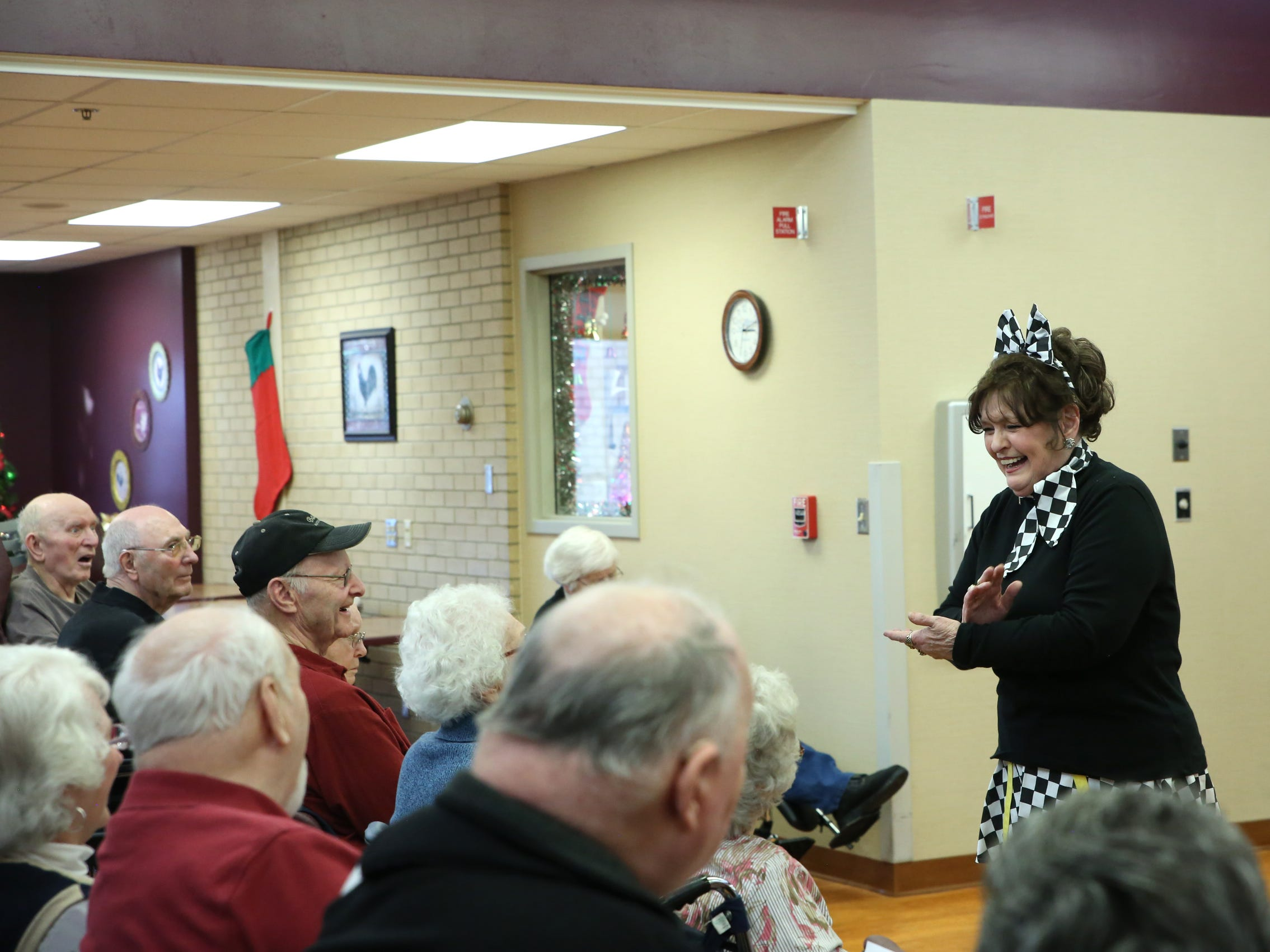 "Joanna Salmon, director of the Dancing Divas, introduces ""Hit the Road Jack"" performance to audience members at Good Samaritan Society-Luther Manor in Sioux Falls, S.D., Friday, Dec. 14, 2018."