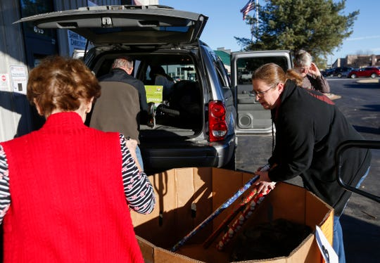 Betsy Stephenson, right, helps volunteers load gifts into her vehicle during the Share Your Christmas distribution at Crosslines on Tuesday, Dec. 18, 2018. Stephenson received gifts for a 12-year-old boy and a 14-year-old girl.