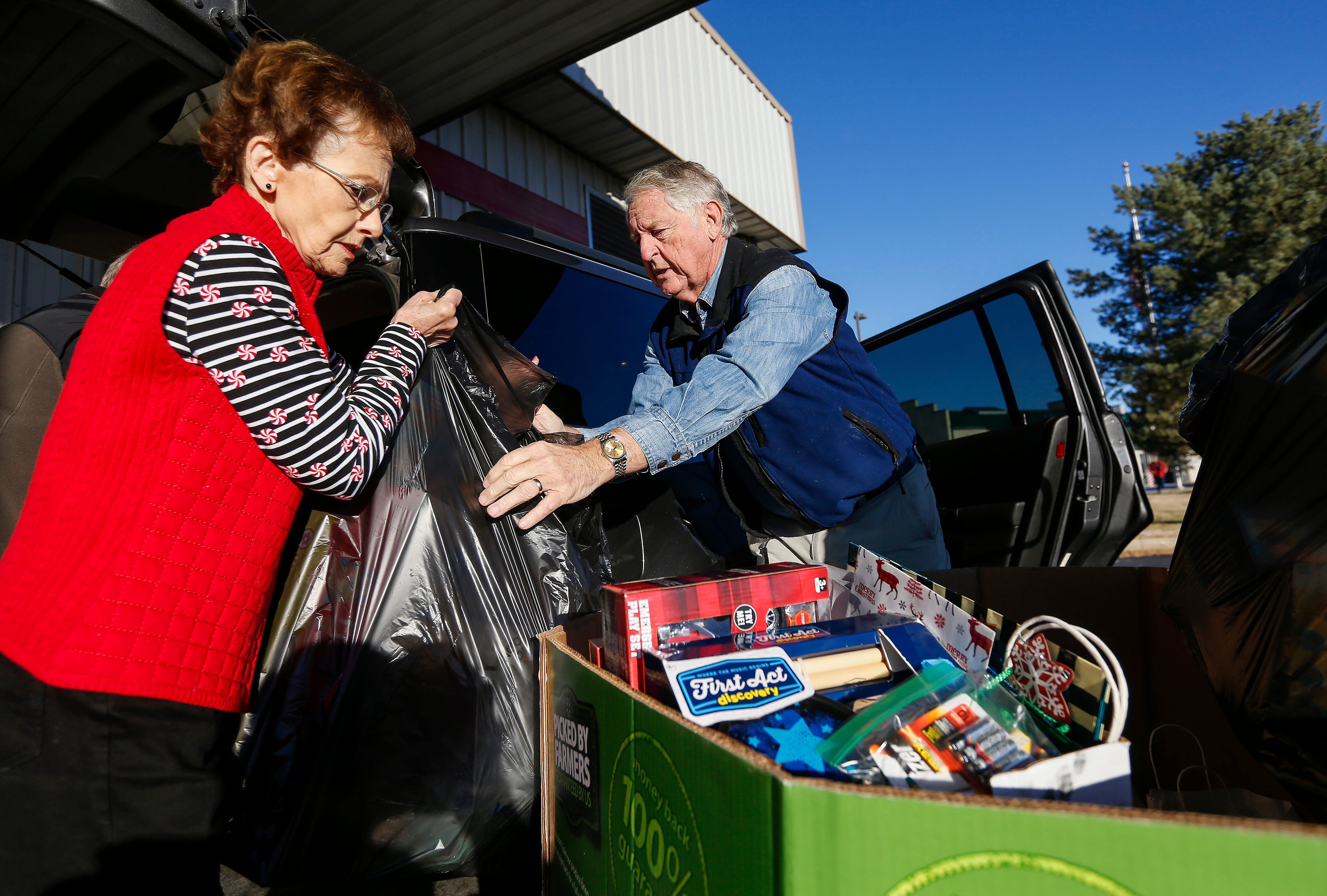 Volunteer Lanny Brent, right, and Sheryl Wachter load gifts into a client's vehicle during the Share Your Christmas distribution at Crosslines on Tuesday, Dec. 18, 2018.