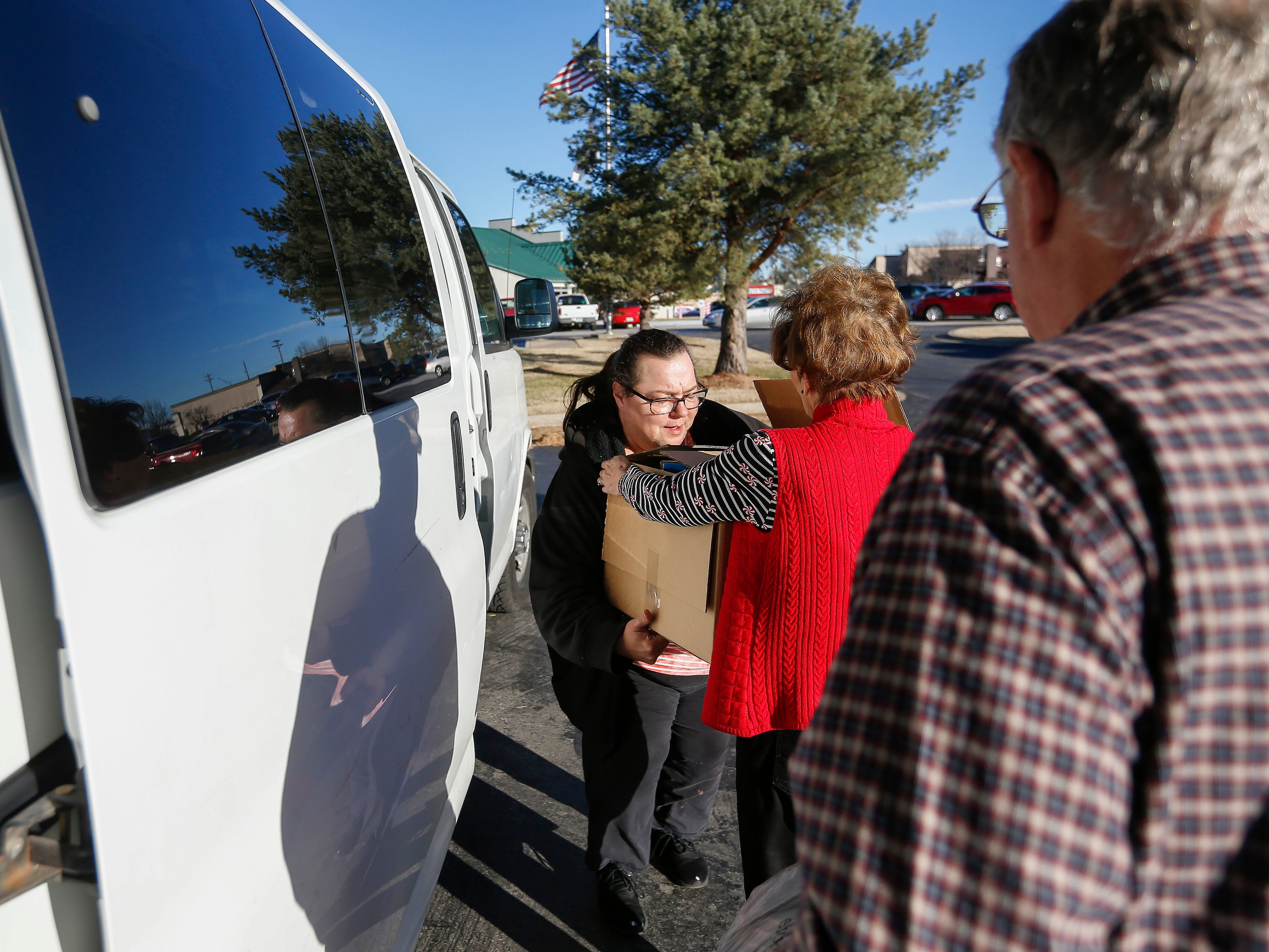 Sheryl Wachter, center, hands a box to  Billie Ridenour as they load gifts into Ridenour's van during the Share Your Christmas distribution at Crosslines on Tuesday, Dec. 18, 2018. Ridenour was receiving gifts for her five grandchildren. Also pictured is Ron Wachter.