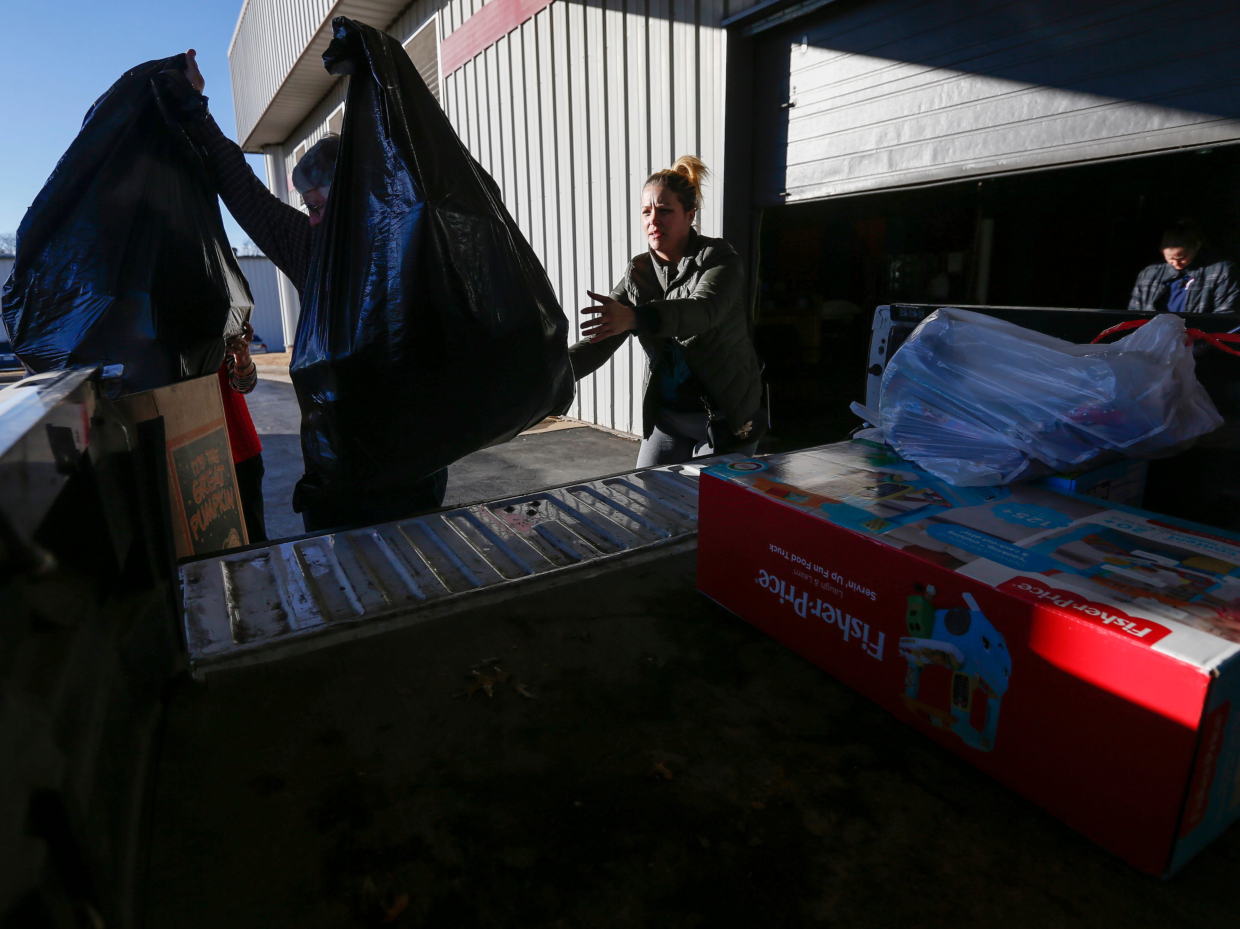 Heather Amundson, right, helps Ron Wachter load gifts into her truck during the Share Your Christmas distribution at Crosslines on Tuesday, Dec. 18, 2018. Amundson was receiving gifts for 2 girls, ages 4 and 3, as well as a 2-year-old boy.