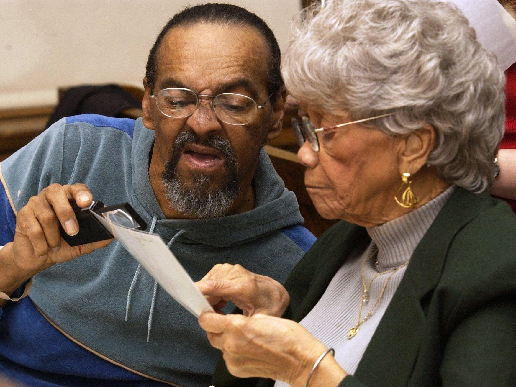 Denny Whayne, left, and Lea Etta McAdams carefully look over old photos as they try to identify people and places in 2006.