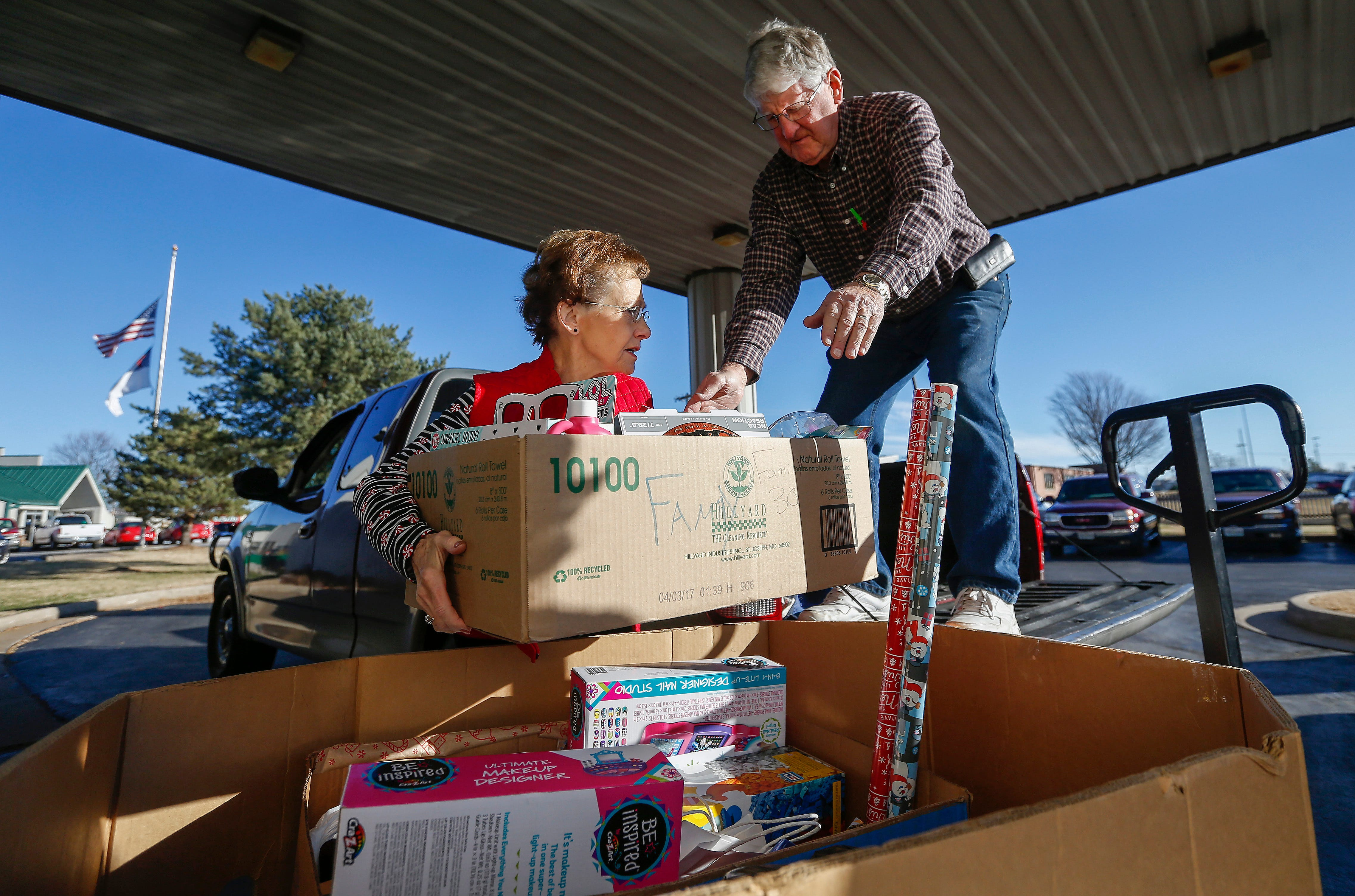 Sheryl Wachter, left, hands a box to her husband Ron Wachter as they load gifts into a client's truck during the Share Your Christmas distribution at Crosslines on Tuesday, Dec. 18, 2018.