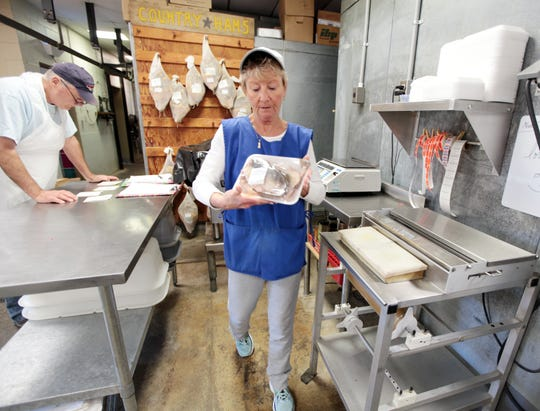 Terri Breeden wraps up two salt fish for a customer at The Meating Place just outside of Staunton on Dec. 7, 2018.