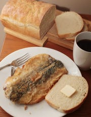 A traditional salt fish breakfast complete with a slice of buttered white bread and a cup of coffee.