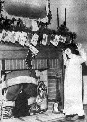"""Christmas Eve 1962 Staunton Leader photo titled, """"An Ahead-of-Schedule Santa Claus."""" The photo, by Ted Riddle, shows 6-year-old Donna Kay Swink of Staunton being astounded by Santa's early arrival down the chimney. Miss Swink was the daughter of Mr. and Mrs. Charles Swink of Lynnhaven Drive."""