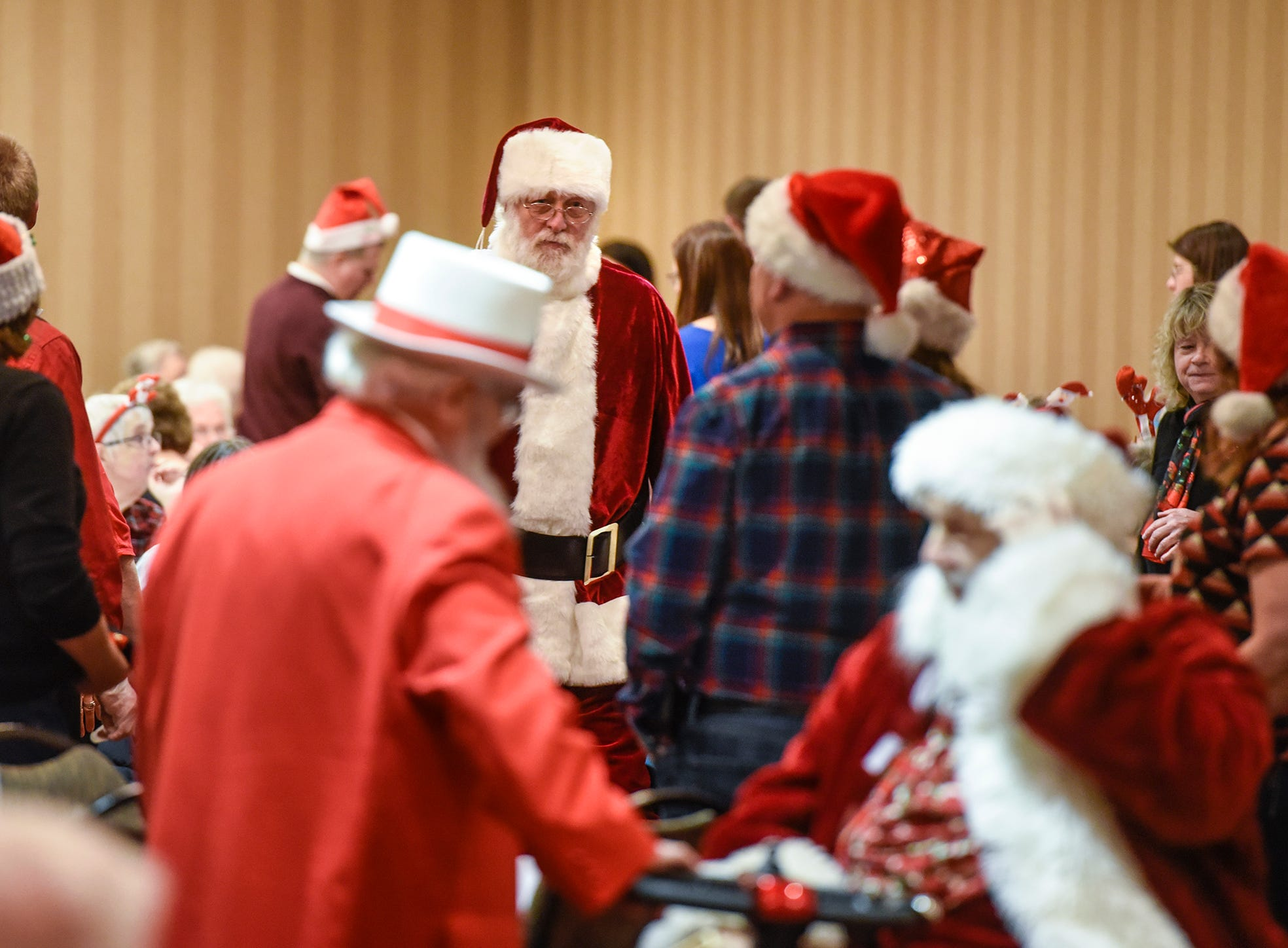 Santas work the room as people take their seats for the Dinner with Santa event Monday, Dec. 17, in St. Cloud.