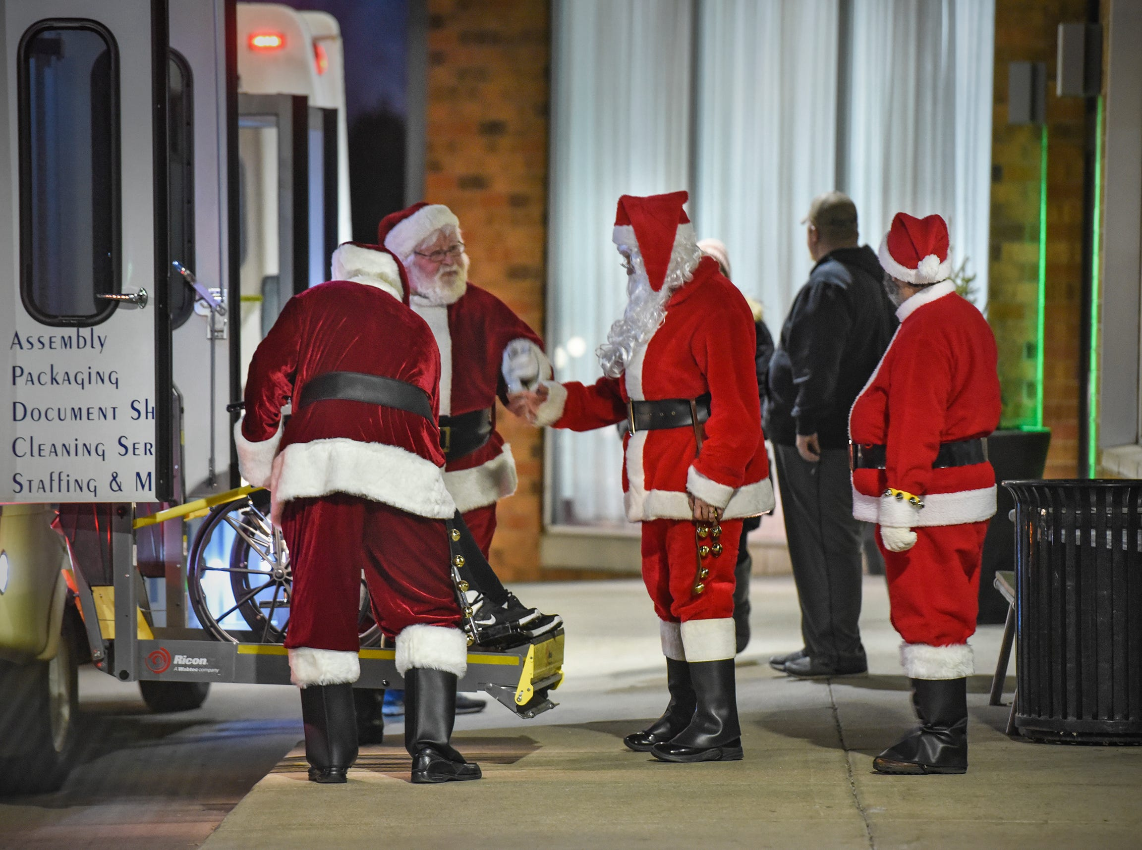 Santas line up to greet people for the Dinner with Santa event Monday, Dec. 17, in St. Cloud.