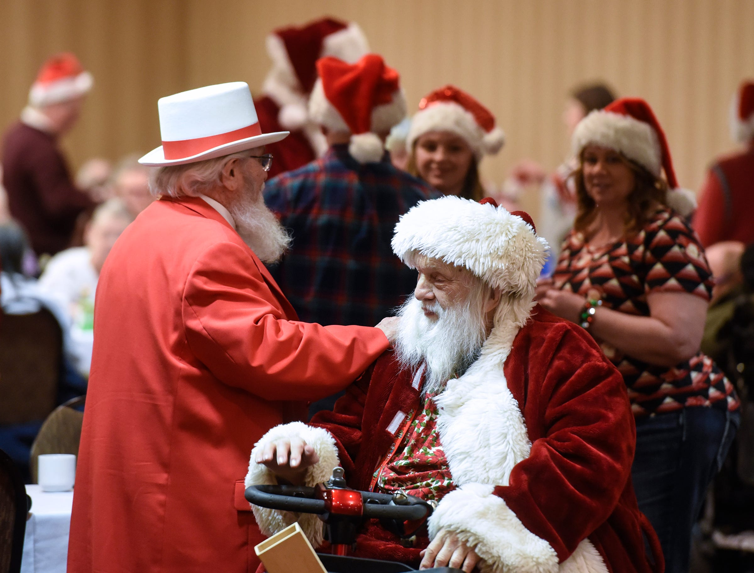 Santas greet the crowd during the Dinner with Santa event Monday, Dec. 17, in St. Cloud.