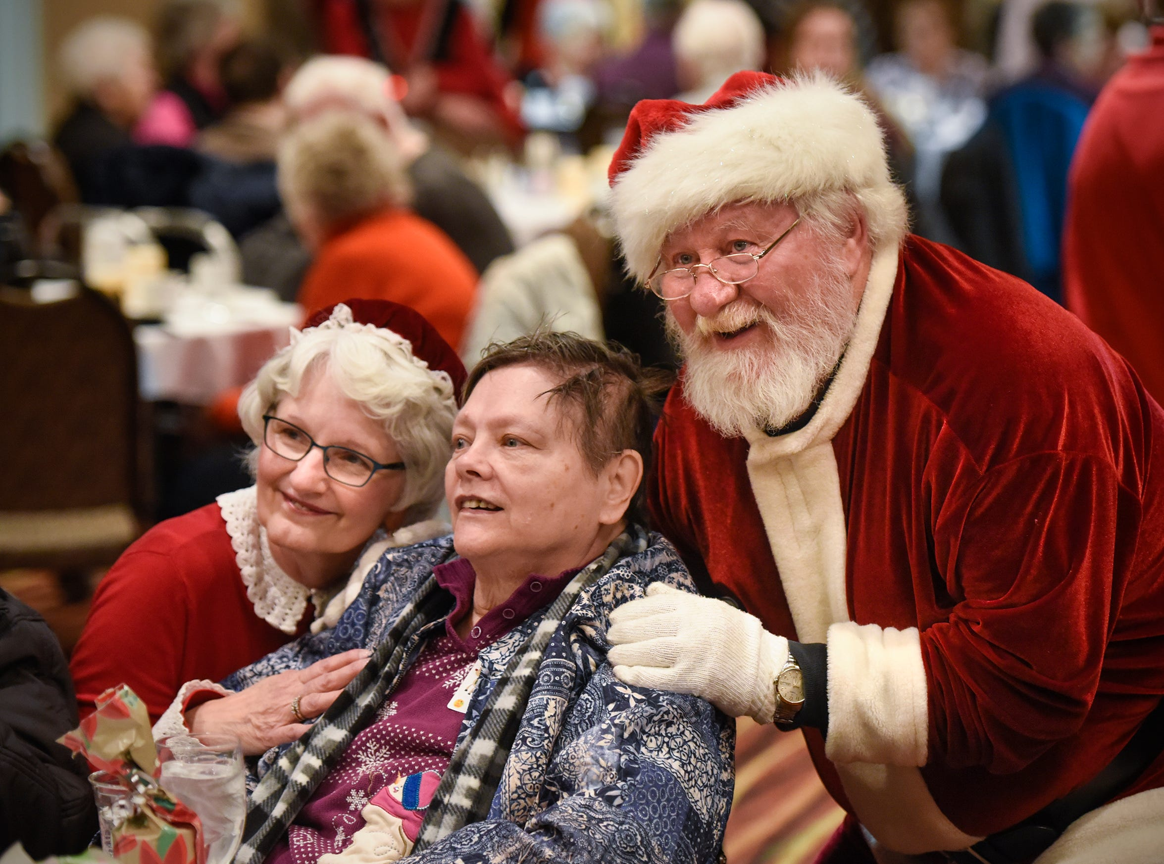 Santa Jerry Stangler and Mrs. Santa Evelyn Budde pose for photographs with people during the Dinner with Santa event Monday, Dec. 17, in St. Cloud.