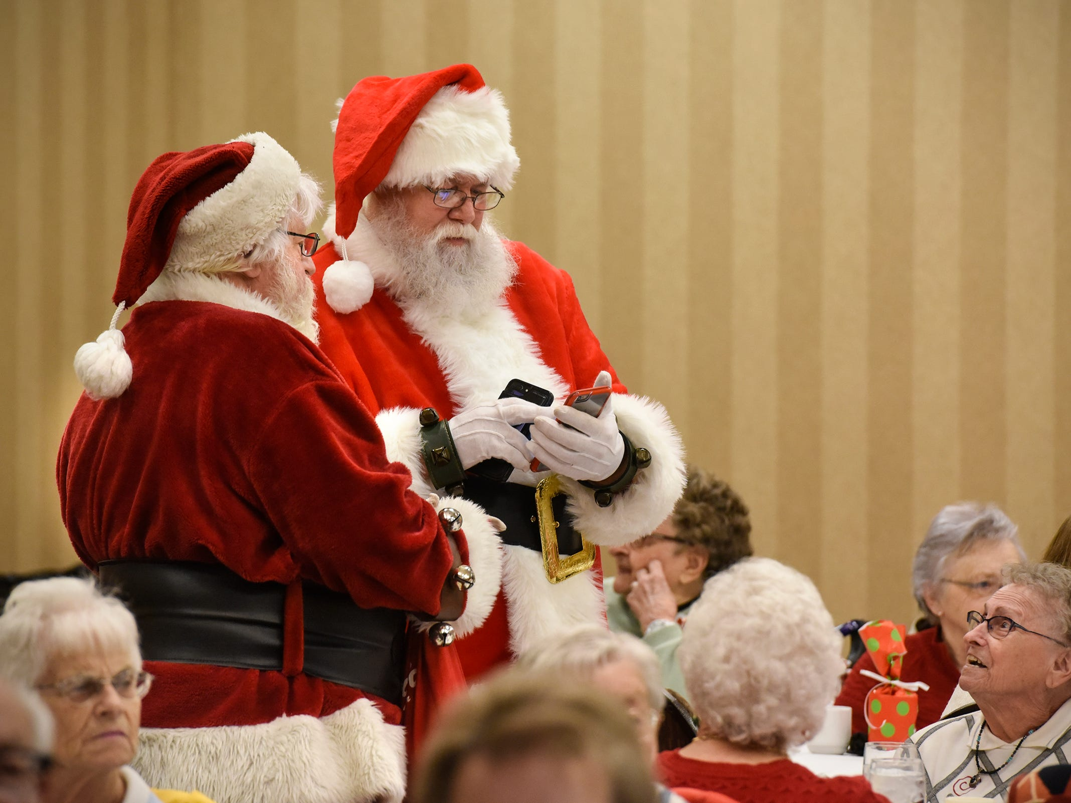 Santas juggle cell phones while taking photos with people during the Dinner with Santa event Monday, Dec. 17, in St. Cloud.