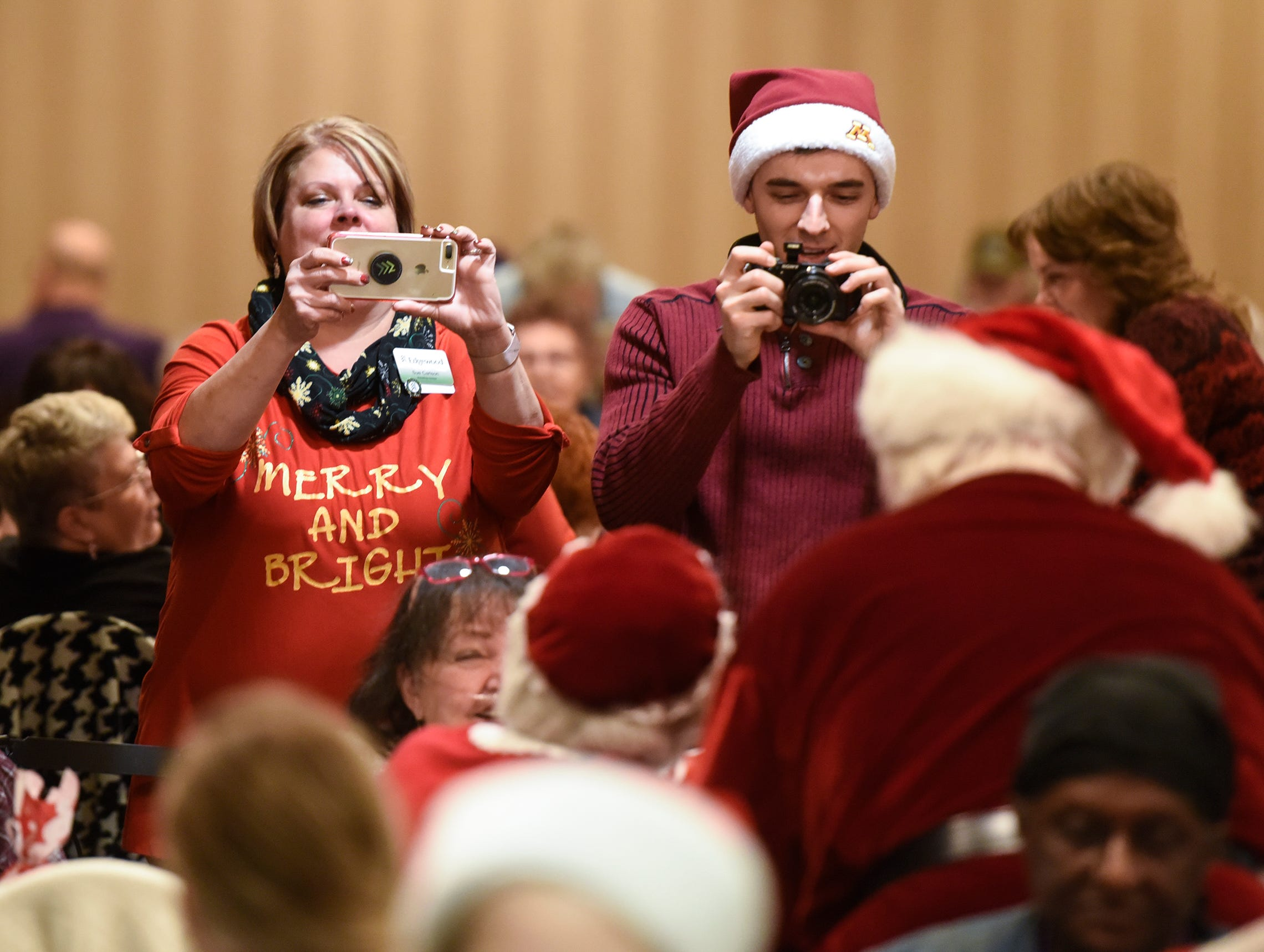 Photographs of residents with Santa and Mrs. Claus are taken during the Dinner with Santa event Monday, Dec. 17, in St. Cloud.