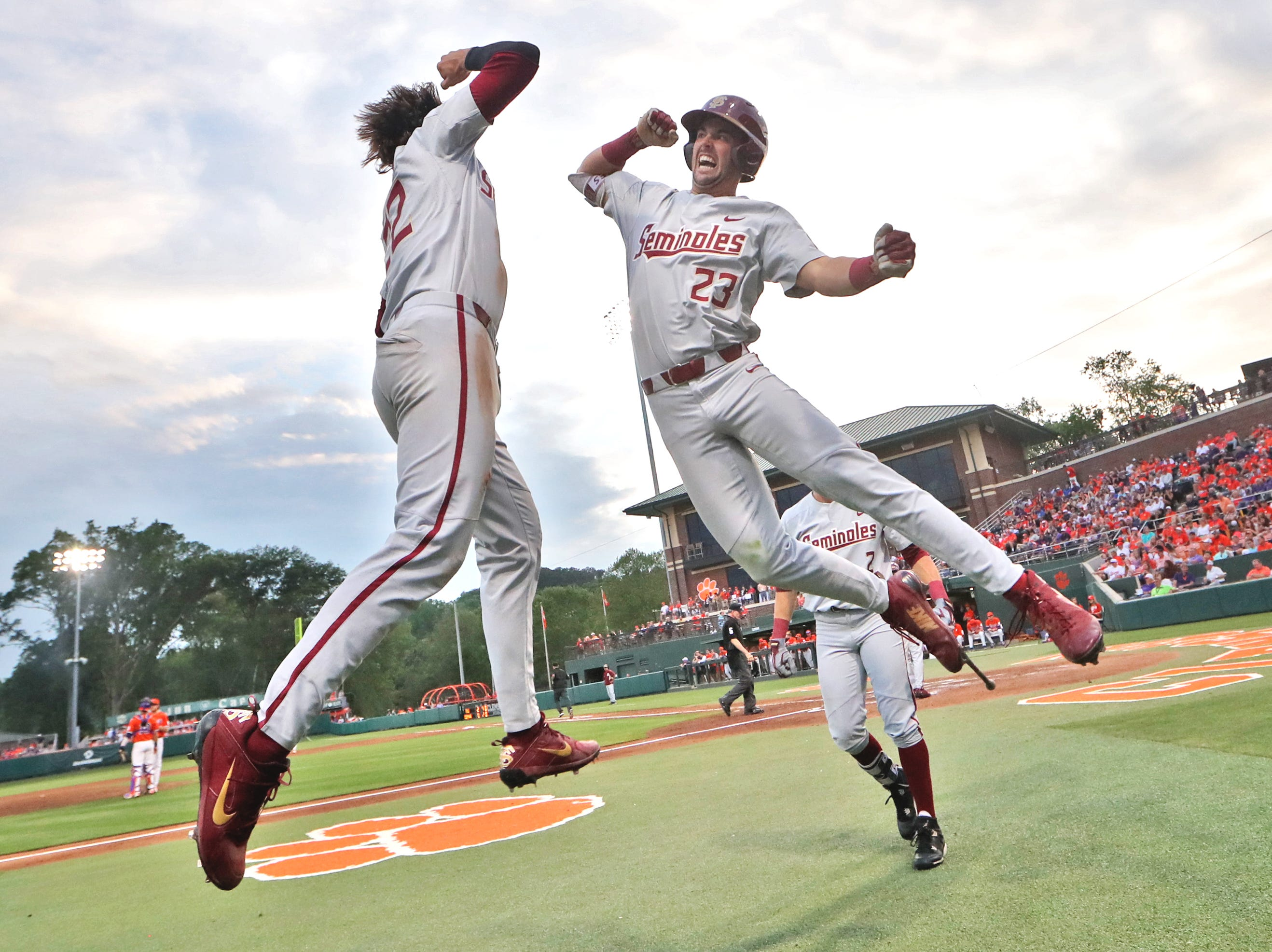 FSU's Drew Mendoza, left, leaps in the air to meet Reese Albert after he hit a solo home run against Clemson at Doug Kingsmore Stadium in Clemson, S.C. on Saturday, May 5, 2018.