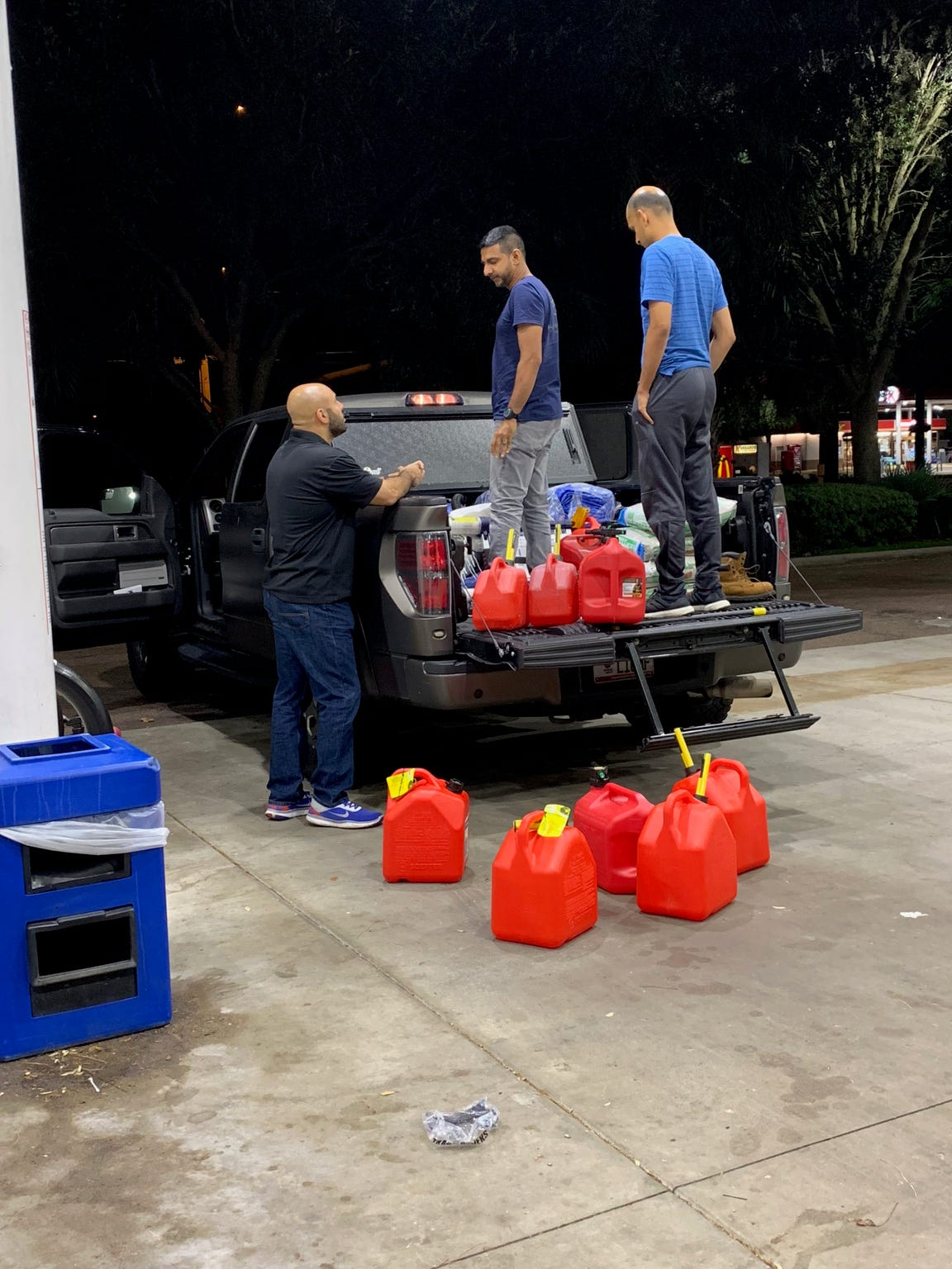Mohammad Sherif, far left, prepares to load fuel containers during a relief trip to Panama City.