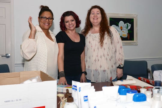"""Diana Wood, left, Olivia DeHavilland and Christine Hasala helps wrap """"Be a Santa to a Senior"""" gifts at the Council on Aging's headquarters in St. Lucie County."""