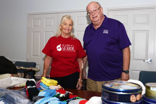 """Diane Donahue and Gregory A. Patrissi of Home Instead help wrap """"Be a Santa to a Senior"""" gifts at the Council on Aging's headquarters in St. Lucie County."""