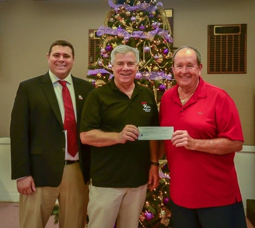 From left, Guardian ad Litem Circuit Director Paul Nigro, and Voices for Children President Robert Perry, receive a donation from PSL Newcomers Club President Greg Snider.