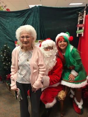 Everyone's a kid at heart when they see Santa! Anonymous Bealls shopper who happened along, Santa, and Evie Klaassen, Santa's elf.