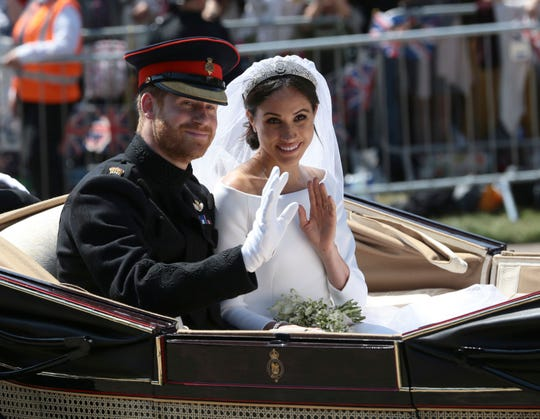 In this May 19, 2018, file photo, Britain's Prince Harry and Meghan Markle ride in an open-topped carriage after their wedding ceremony at St. George's Chapel in Windsor Castle in Windsor, near London.