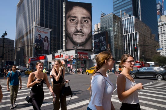 "In this Sept. 6, 2018, file photo, people walk by a Nike advertisement featuring Colin Kaepernick in New York. In his ""Just Do It"" spot for Nike that marked the campaign's 30th anniversary in September, the sidelined-by-kneeling NFL quarterback somberly challenged viewers to ""believe in something, even if it means sacrificing everything."" Some responded with anger, cutting or burning Nike gear and calling for boycotts."