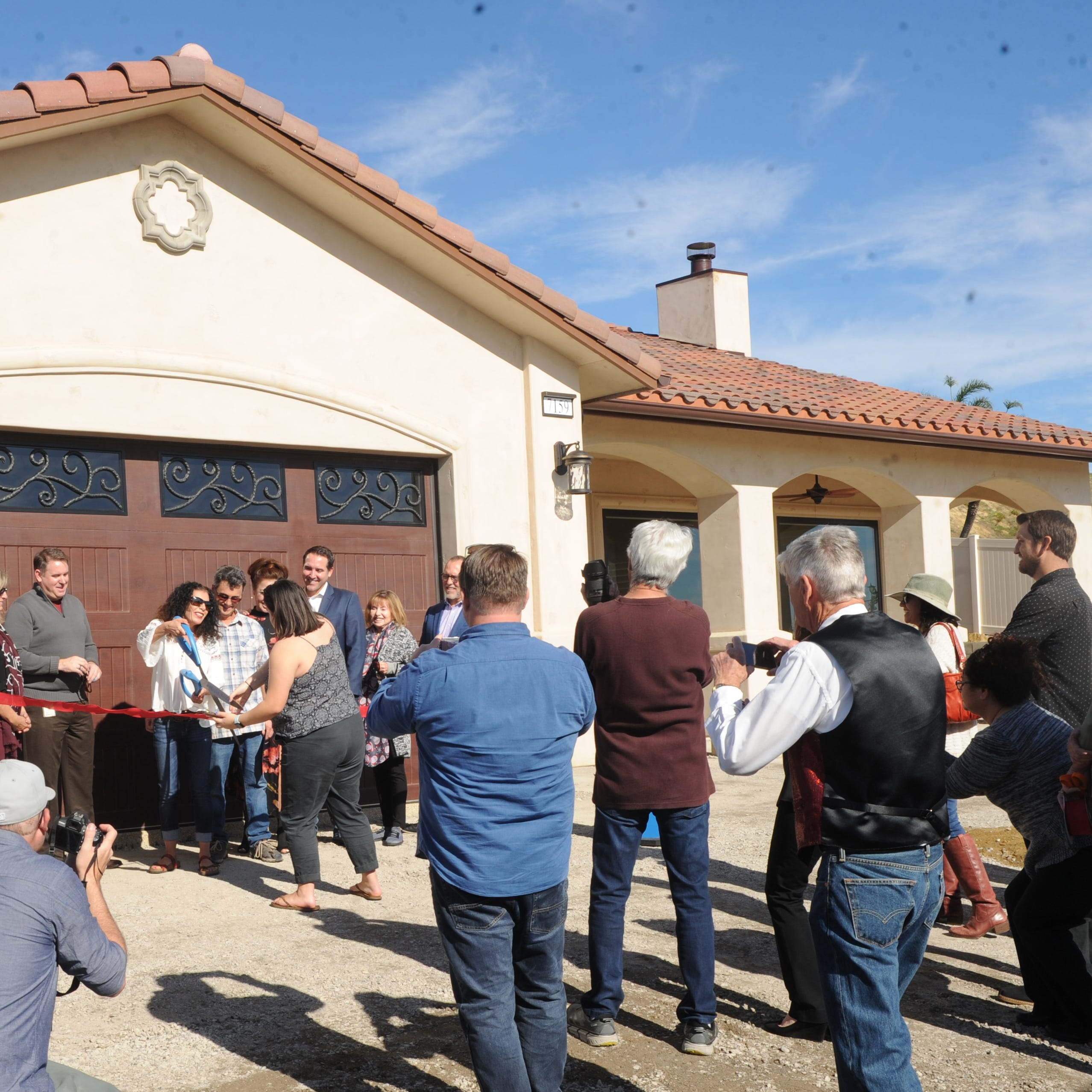 Sandra Gustafson and her husband, Michael Gustafson, who lost their home in the Thomas Fire, celebrate the completion of their new home with a ribbon-cutting ceremony Tuesday morning in Ventura.