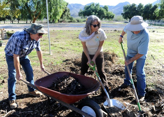 From left, development manager Dennis Perry, Ventura County Supervisor Linda Parks and Steve Sandifer, demonstration garden designer, shovel material to the newly built compost pile at Growing Works near Camarillo.