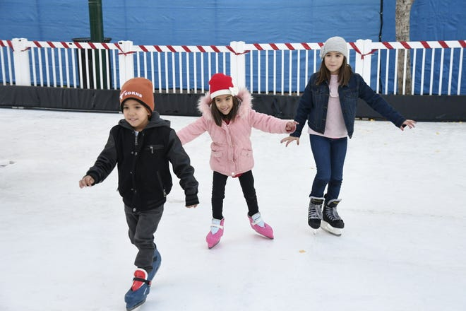 Siblings A.J. Flores, 4, Aubrie Flores, 6, and Natalie Flores, 9, skate together at the grand opening of Ice Skate Visalia on Sunday, December 2, 2018.