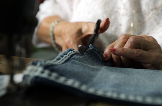 Catherine Villanova, 96, cuts a pair of jeans to be hemmed at The Laundry Room in Mahopac, her son's laundry busness. Villanova worked at an aircraft plant during World War II.