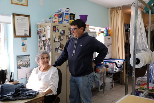 Catherine Villanova, 96, with her son, Bill, at The Laundry Room in Mahopac. Behind her is a Rosie the Riveter sign and a letter that commends her service.