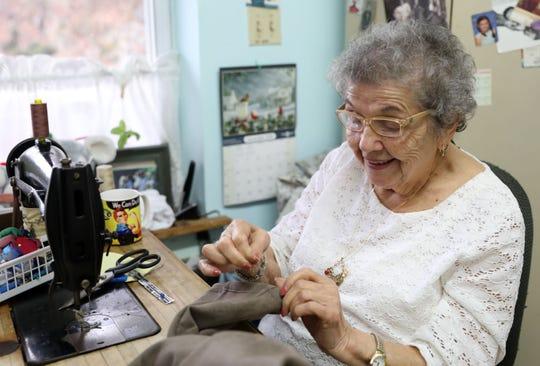 Catherine Villanova, 96, hems a pair of pants at The Laundry Room in Mahopac, where she works several days a week. On her sewing table is a Rosie the Riveter mug. Villanova worked at an aircraft plant during World War II.